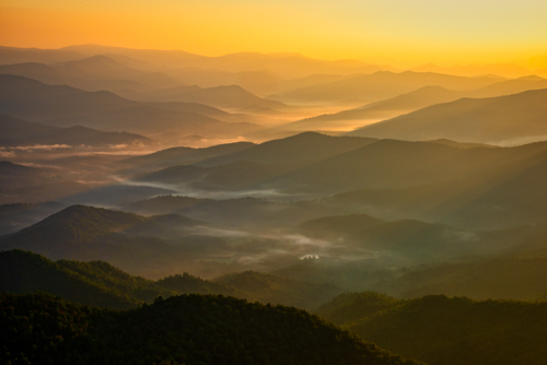Photograph of the Smoky Mountains mist at sunrise over Brasstown Bald by Andy Crawford