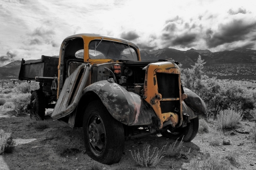 Black & white and color photograph of an old car in front of the Sangre de Cristo Mtns. by Dave Maes