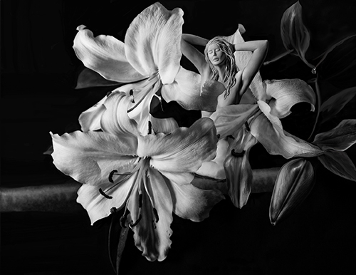 Black and White photograph of a sculpture of a female nude and flowers by Bonnie Kamhi