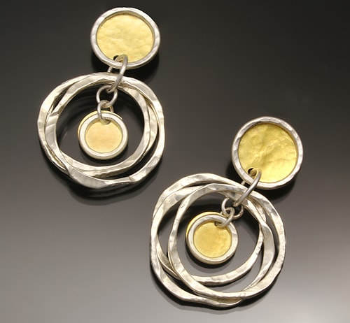 a pair of hand made silver and gold dangle earrings by Sana Doumet